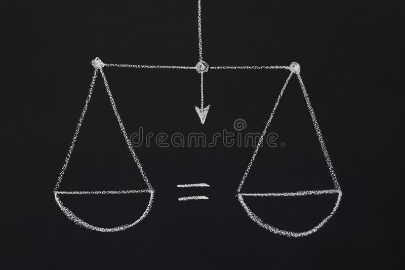 Drawn scales with equal scalepans on black chalkboard royalty free stock photo
