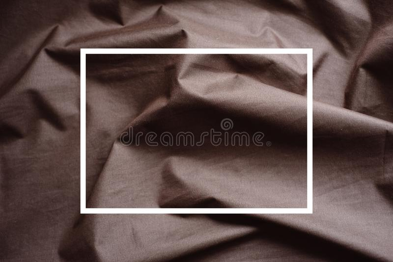 Drawn white frame against a background folds of brown fabric. Creative layout. Texture use as an abstract background. Luxurious royalty free stock photo