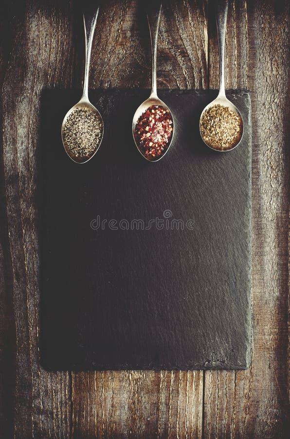 Draygewürze auf Metalllöffel auf schwarzem Stein mit Kopienraum Woode lizenzfreie stockbilder