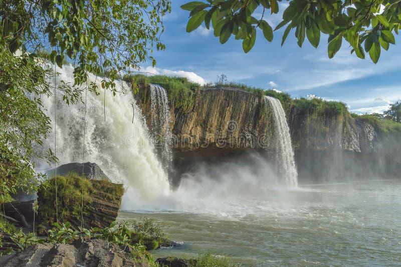 DrayNur vattenfall, mot en bakgrund av grön vegetation, blå himmel och moln royaltyfri fotografi