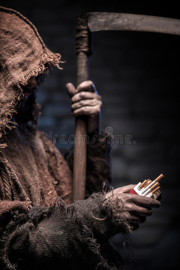 Dreadful death with scythe is waiting for smoker. Grim Reaper is holding a pack of cigarettes and proposing it to someone. The man is standing with seriousness royalty free stock photography