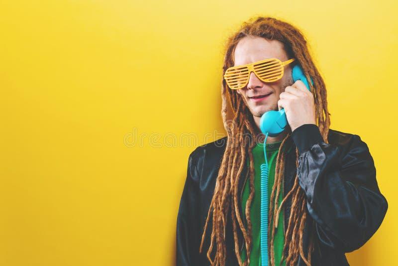Dreadlocked man som talar på den gamla retro telefonen arkivfoton