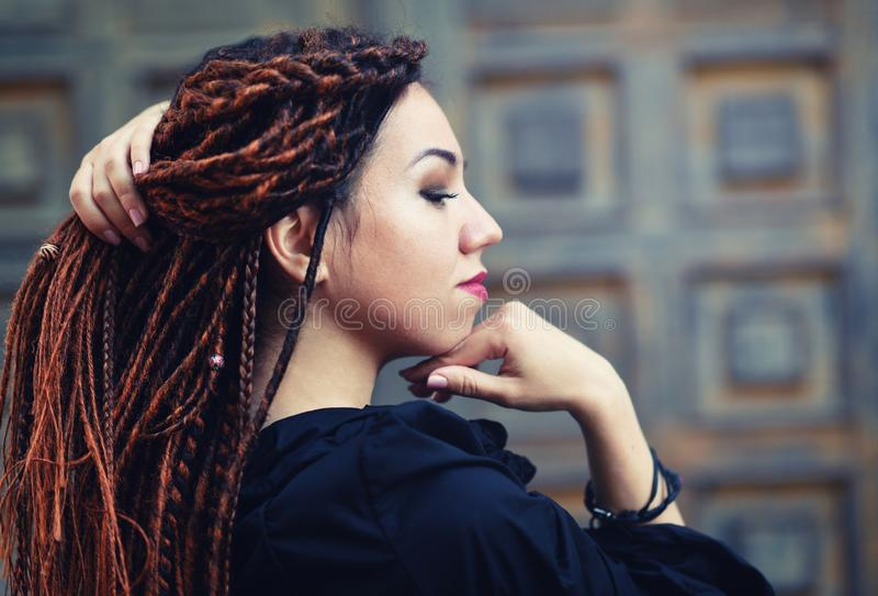 Dreadlocks closeup, fashionable girl posing at old wooden door background royalty free stock image