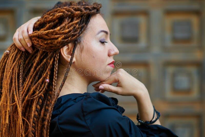 Dreadlocks closeup, fashionable girl posing at old wooden door background royalty free stock photo
