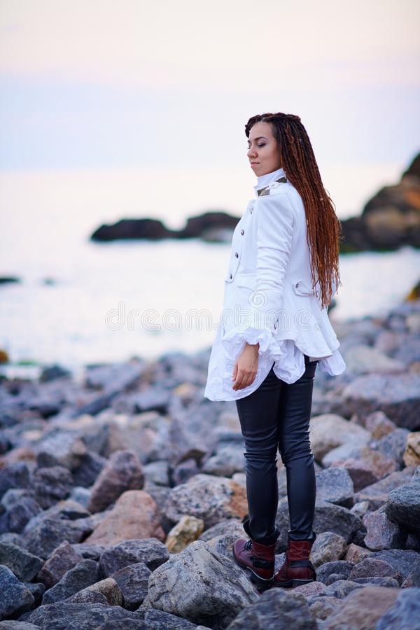 Dreadlocks fashionable girl dressed in white jacket and black leather trousers posing near sea in the evening stock images