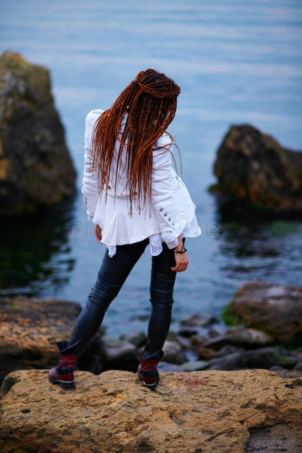 Dreadlocks fashionable girl dressed in white jacket and black leather trousers posing near sea in the evening royalty free stock image