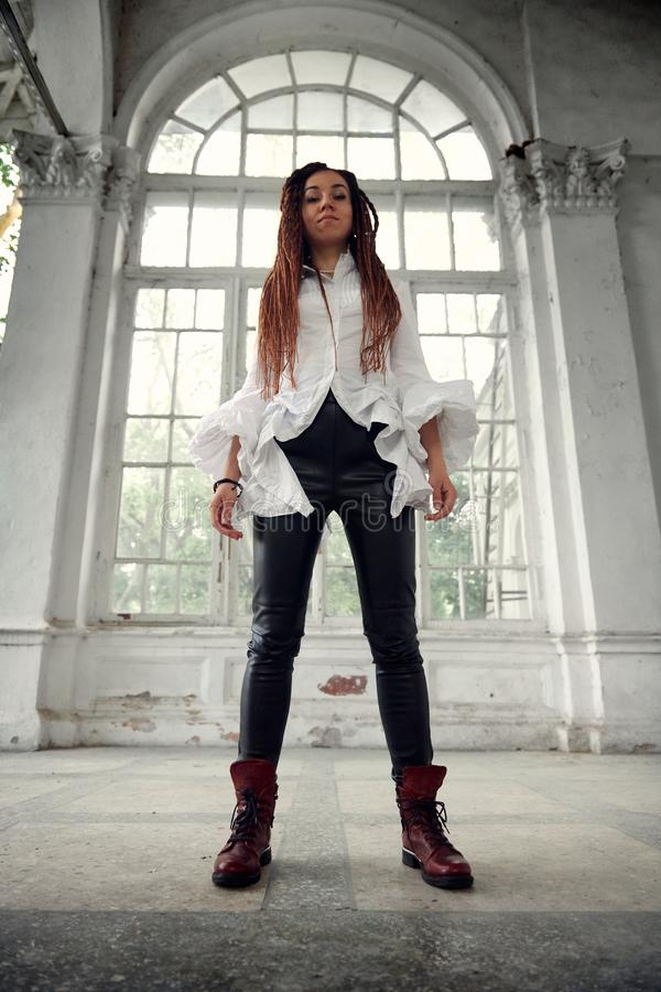 Dreadlocks fashionable girl dressed in white shirt and black leather trousers posing in font of old big window royalty free stock photography