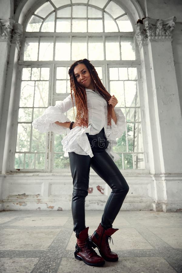 Dreadlocks fashionable girl dressed in white shirt and black leather trousers posing in font of old big window royalty free stock images