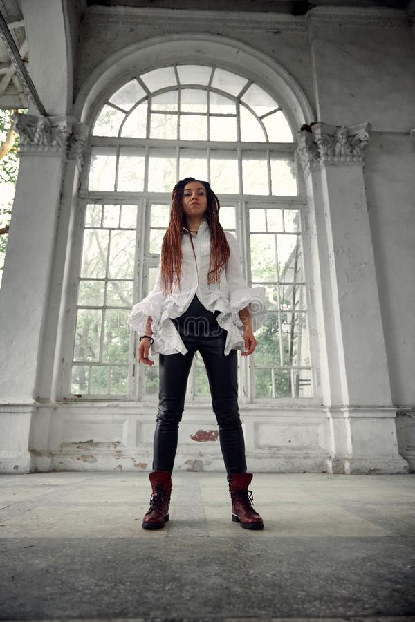 Dreadlocks fashionable girl dressed in white shirt and black leather trousers posing in font of old big window stock image