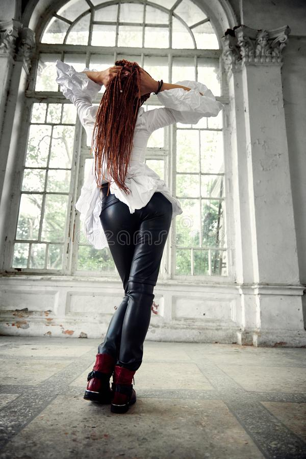 Dreadlocks fashionable girl dressed in white shirt and black leather trousers posing in font of old big window, rear view stock photos