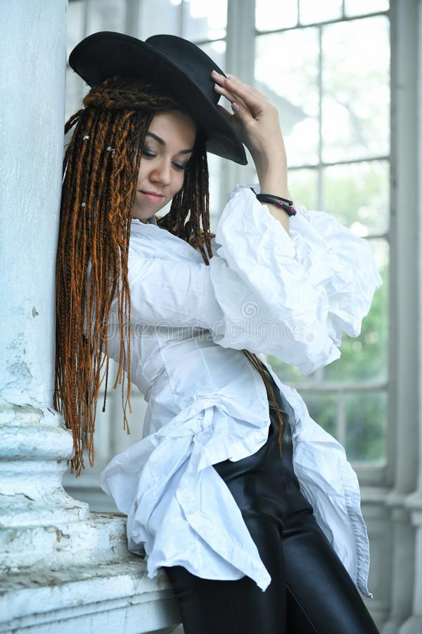 Dreadlocks fashionable girl posing near old white house, dressed in black hat and leather trousers stock photography