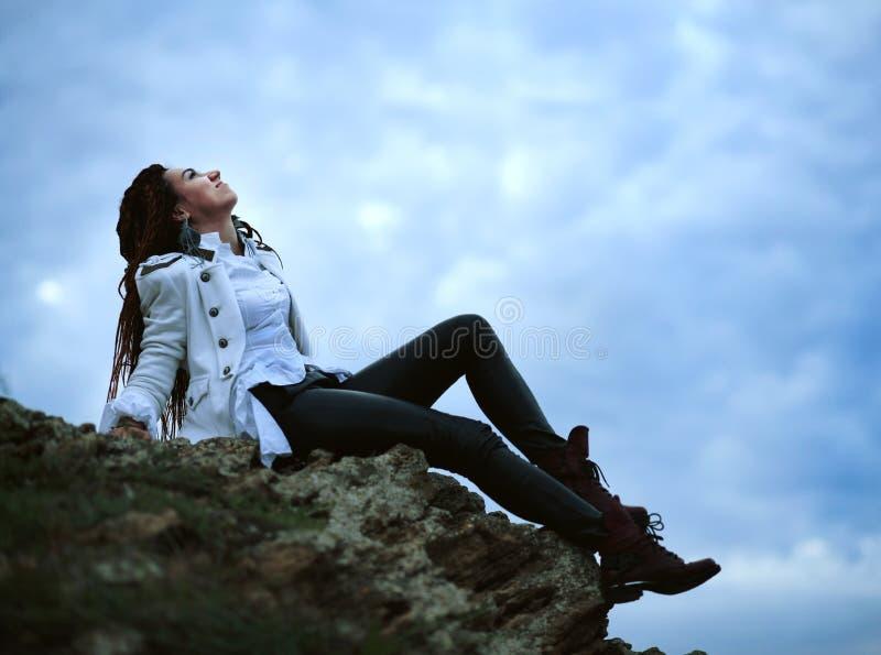 Dreadlocks fashionable girl posing near sea at sunset, sits on high stone on sky background royalty free stock image