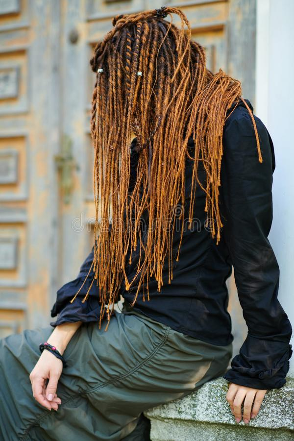 Dreadlocks fashionable girl posing at old wooden door background. side view with no face visible royalty free stock images