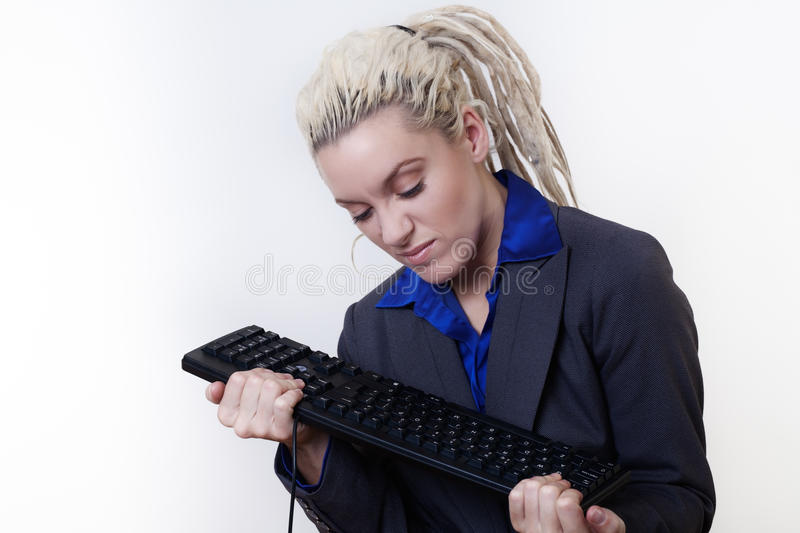Dreadlocks at work. Business person with dreadlock hair getting mad at her keyboard at work royalty free stock photography