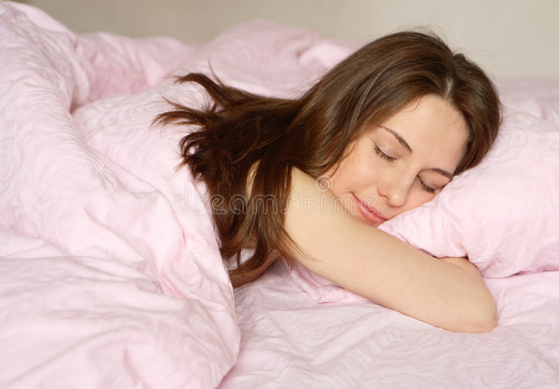 Dream. The girl sleeps on pink bed-clothes stock photos