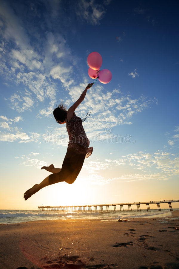 Dream balloons. Girl flying with balloons at sunset beach stock photos