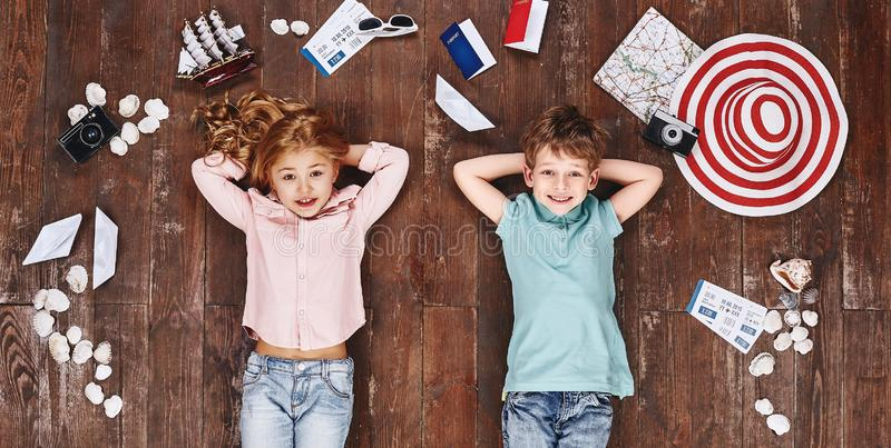 Dream big. Children lying near travel items, looking at camera and smiling stock photos