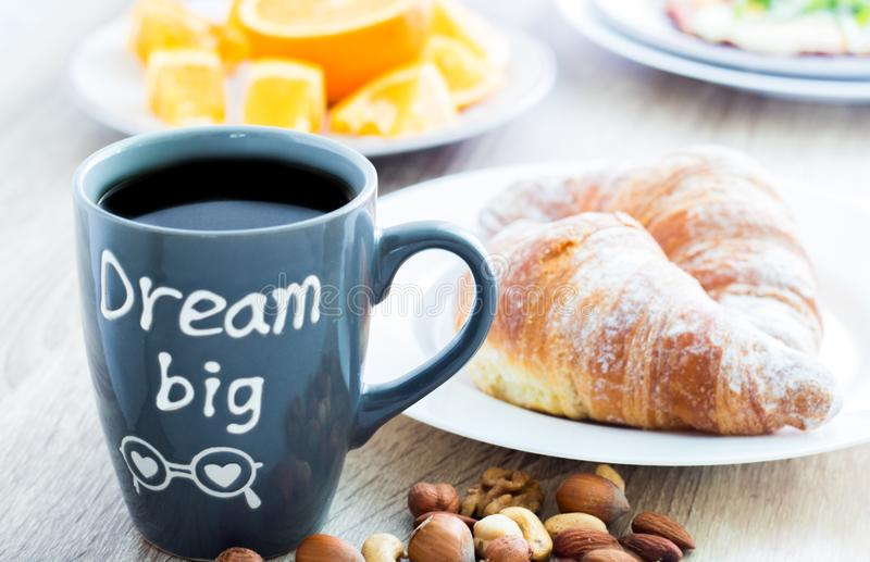 Dream big. Good morning breakfast. Mug of coffee with croissants, nuts and oranges. Dream big. Good morning breakfast. Mug of coffee with croissants, nuts and stock photo