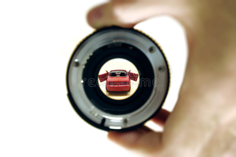 Dream car. This photograph represent a man looking through a lens to its dream car. Great concept for your brochure, print advertising and other media royalty free stock image