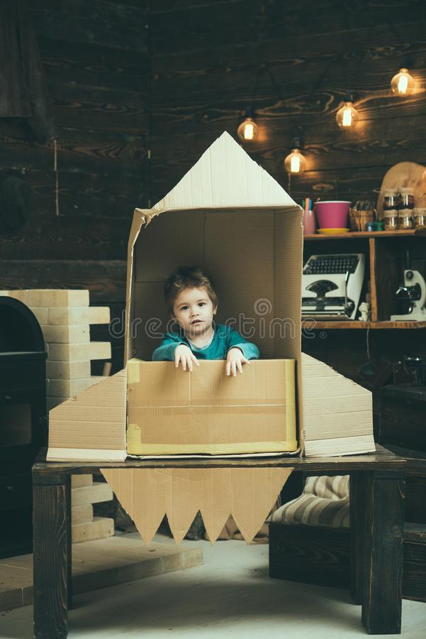 Dream about career of cosmonaut. Small boy play in paper rocket, childhood. Your dreams may come true. Travel and royalty free stock images