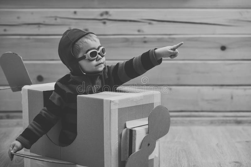 Dream, career. Little boy child play in cardboard plane, childhood stock photography