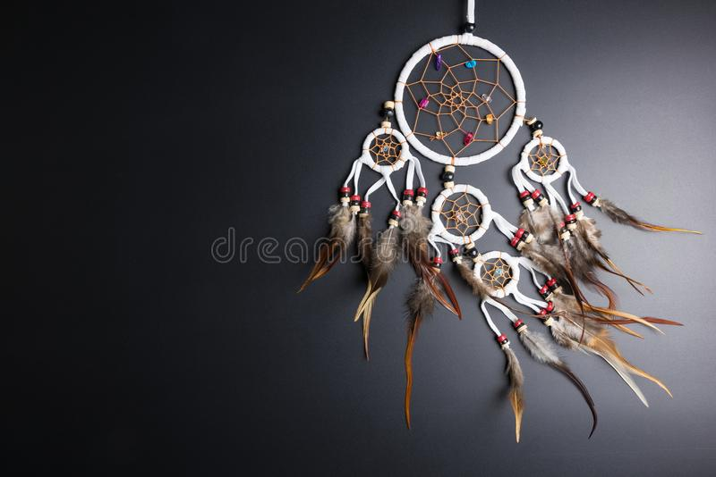 Dream catcher with feathers threads and beads rope hanging spiritual folk american native indian amulet isolated on black stock image