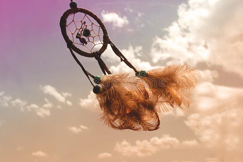 Dream catcher flying over a cloudy -colourful sky. The sky is tainted of several colours such as purple, brown or blue stock photography