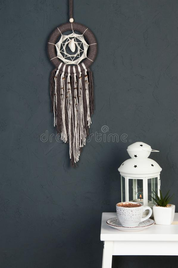 Dream catcher on gray. Beige brown dream catcher and white bedside table in bedroom decor on dark gray textured background. Copy space for text stock photography