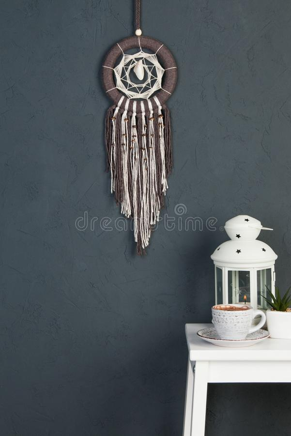 Dream catcher on gray. Beige brown dream catcher and white bedside table in bedroom decor on dark gray textured background. Copy space for text royalty free stock image