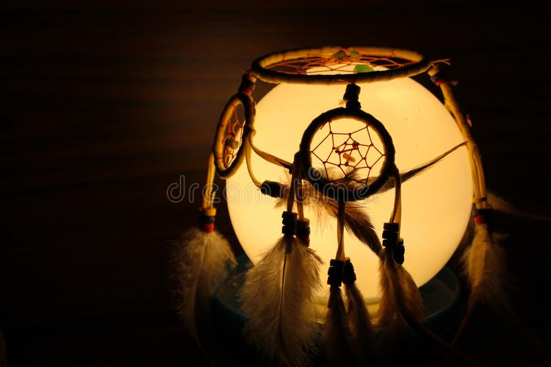 Dream catcher placed on light bowl in the dark stock image