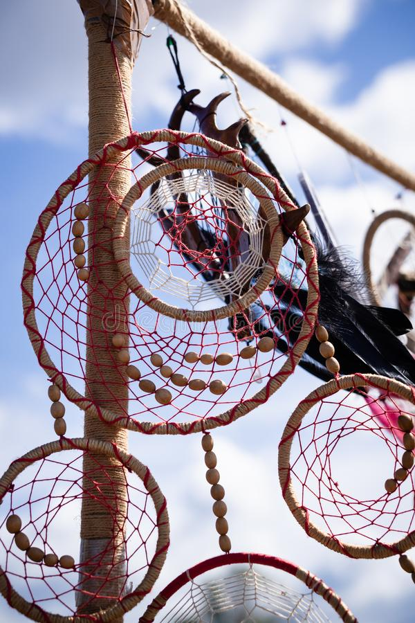 Dream catcher with red threads, beads and feathers of white, pink and black stock images