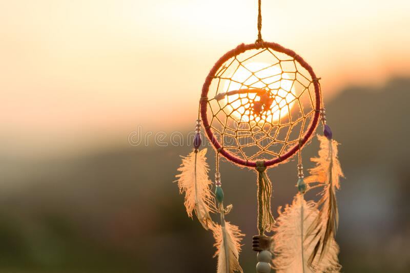 Dream cathcher amulet with sunset in background.Dream catcher is a handmade willow hoop woven to a web or literally  includes such. Features as feathers and stock images