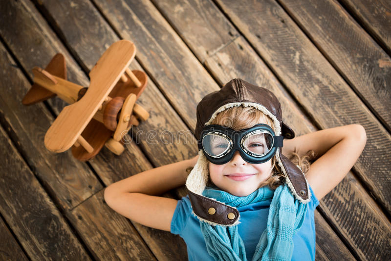 Dream. Child pilot with vintage plane toy on grunge wooden background stock images