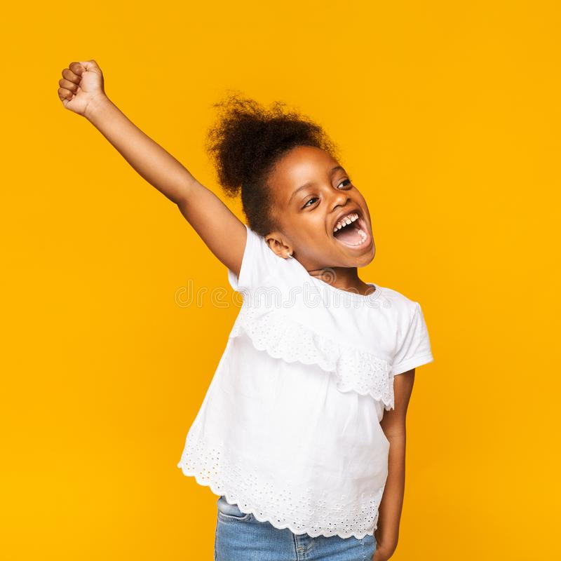 Cute african toddler girl shouting hooray on orange background royalty free stock images