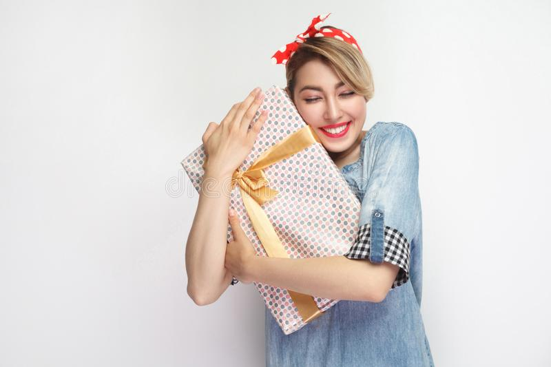 Dream come true! Satisfied young woman in casual blue denim shirt and red headband standing, hugging her present with closed eyes stock image
