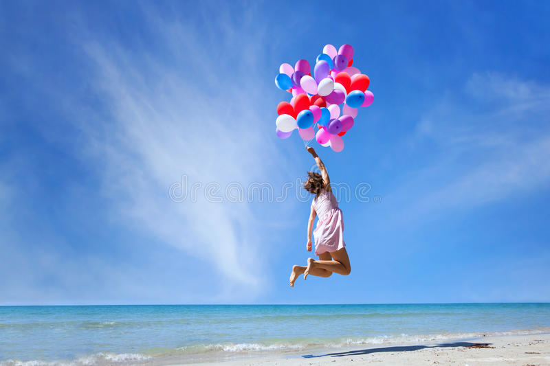 Dream concept, girl flying on multicolored balloons. In blue sky, imagination and creativity royalty free stock image