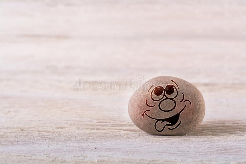 Dream emoticon. Stone face on white wood background with free space for your text stock images