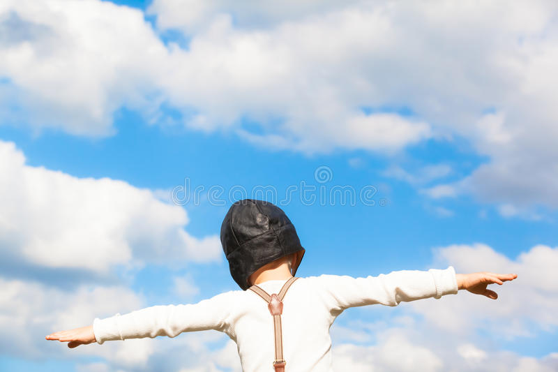 Dream of Flying. Little boy in vintage clothes (grandad shirt, suspenders, aviator hat) dreams of flying with outstretched arms in front of the cloudy sky (copy royalty free stock photography