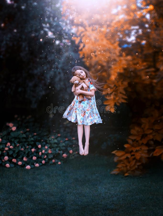 Dream of girl with flying hair hovers above ground with teddy bear in hands. Dream of cute girl with flying hair hovers above ground with teddy bear in hands royalty free stock photos