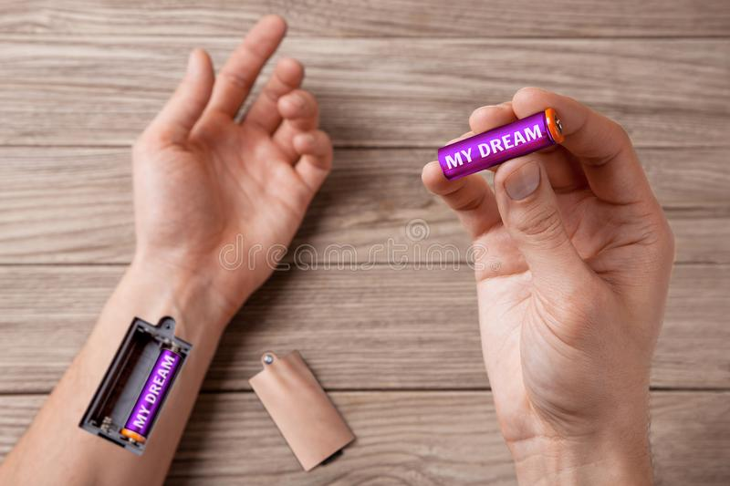 Dream gives strength and energy moves on. Word my dream is written on the battery. Hand of man with a slot for charging batteries. royalty free stock photography