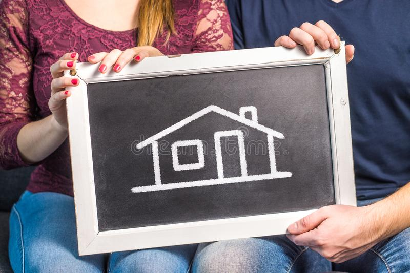 Dream house, home insurance, interior design or future planning. Concept. Happy couple, men and woman, holding blackboard with drawn house stock photography