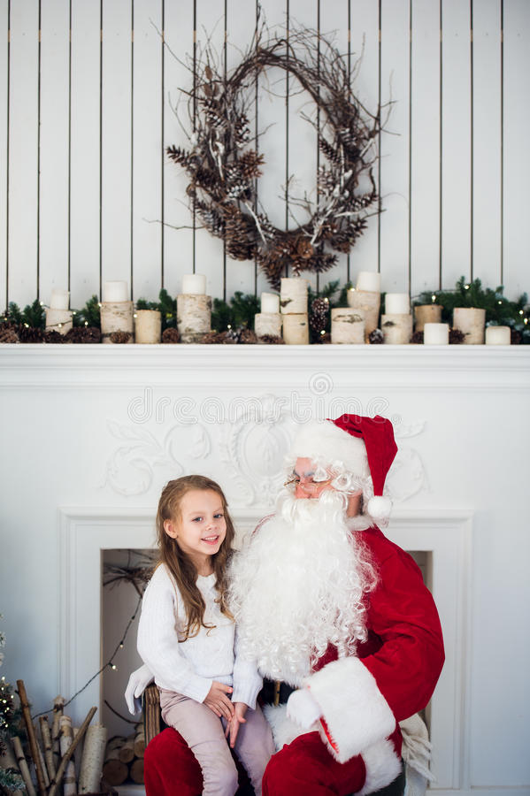 Dream is real in christmastime. happy little cute girl sitting on the lap of aged Santa Claus and hugs at home near stock photo