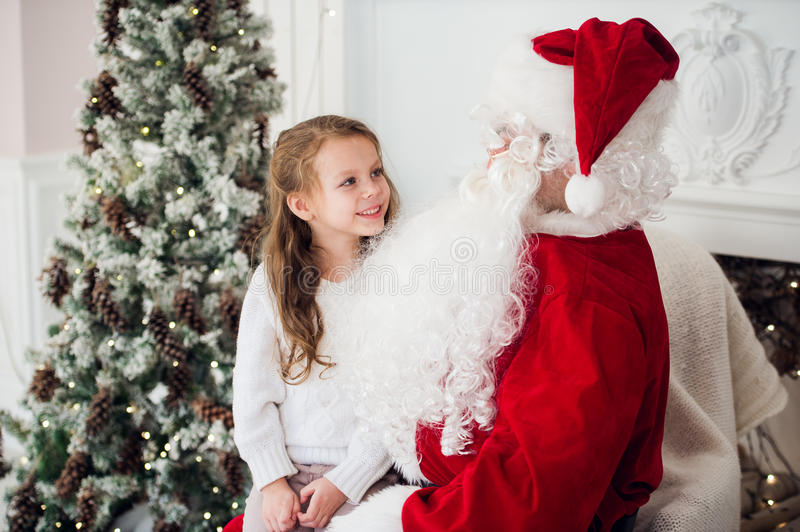 Dream is real in christmastime. happy little cute girl sitting on the lap of aged Santa Claus and hugs at home near royalty free stock photos
