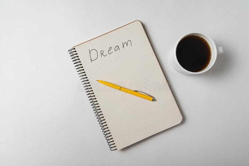 Dream reminder notice. Copybook with pen and cup of coffee on white background. Top view stock image