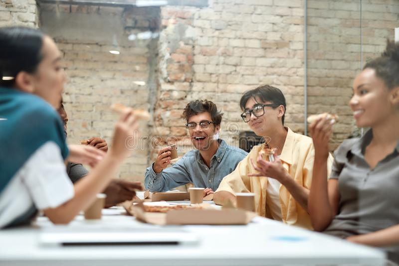 Dream team. Group of positive young coworkers eating pizza and talking with each other while having lunch together in stock image
