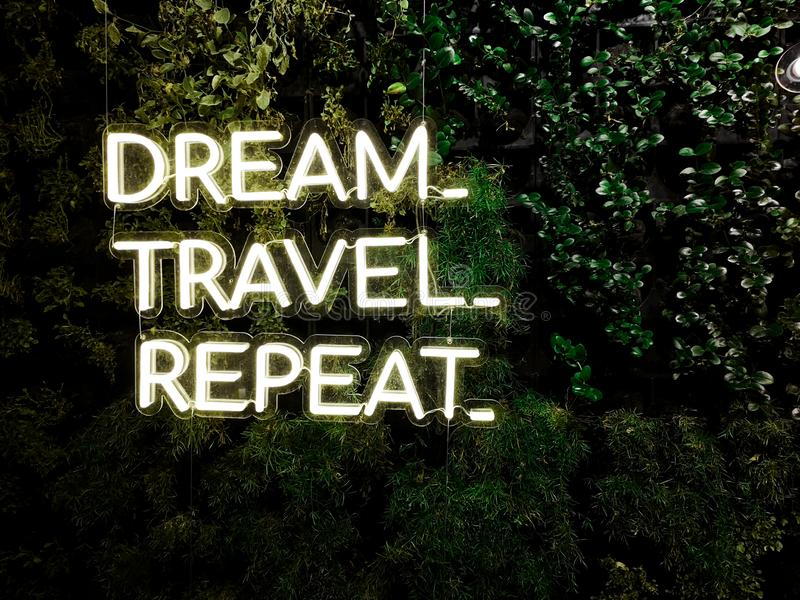 `Dream, Travel, Repeat` quote - Neon cool inspiring quote about travel and dreams royalty free stock images