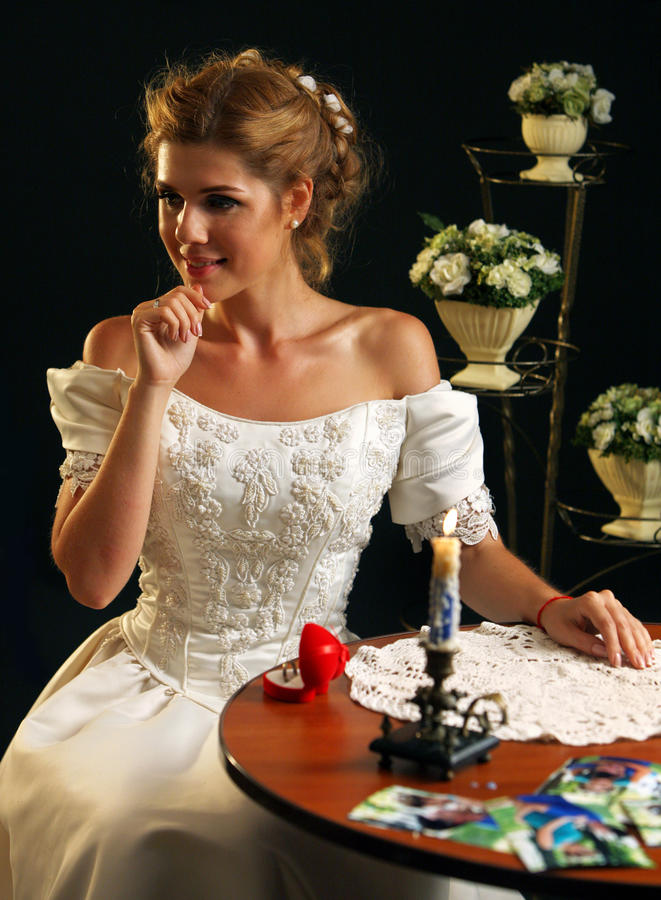 Dream wedding about ceremony. Girl in wedding-dress. Dream wedding about ceremony. Girl in wedding-dress sits at table next to candle and photos. On table is an royalty free stock image