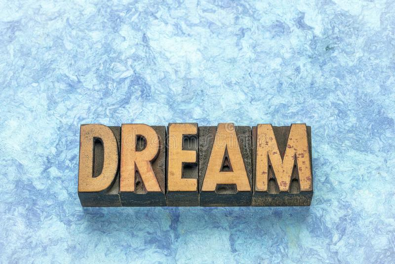 Dream word in letterpress wood type. Dream word in vintage letterpress wood type against blue bark paper stock photo