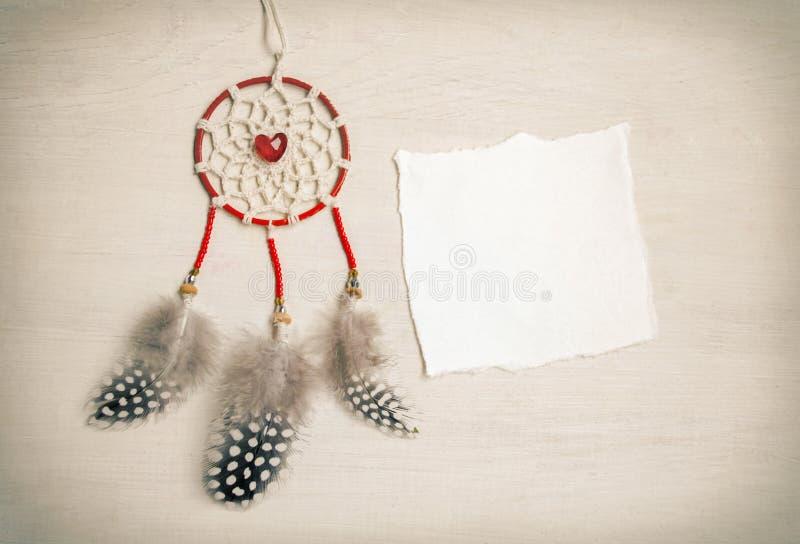 Dreamcatcher με τα φτερά σε ένα ξύλινο υπόβαθρο Εθνικό σχέδιο, ύφος boho, φυλετικό σύμβολο Κόκκινη καρδιά ως σύμβολο του βαλεντίν στοκ φωτογραφία με δικαίωμα ελεύθερης χρήσης