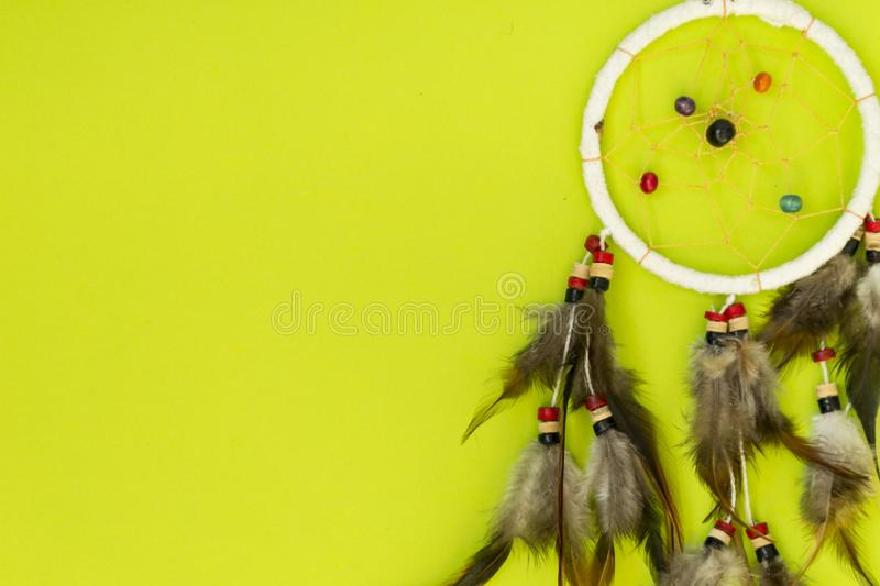 Dreamcatcher with brown bird feathers, and with threads and beads of rope hanging. Dreamcatcher handmade. Lies on a green stock photography